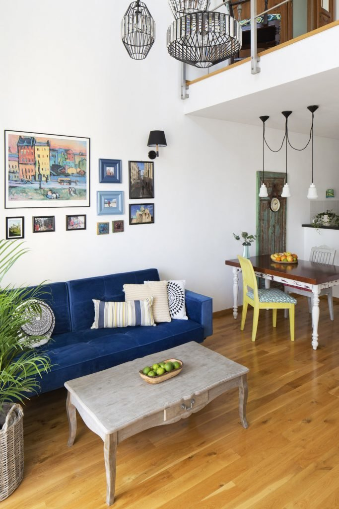 Kolorowe mieszkanie,mieszkanie boho,kolor w salonie, Salon połączony w kuchnią, niebieska kanapa, stół vintage, żółte krzesło, szary stolik kawowy, palma