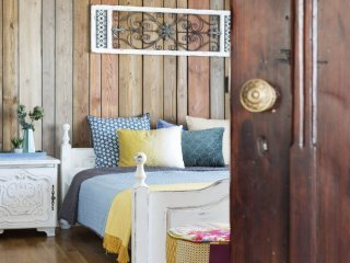 Kolorowe mieszkanie,mieszkanie boho,dekoracja nad łóżkiem panel drewniany,ściana obita drewnianymi dechami w kolorze drewna, niebieskie kinkiety vintage, rzeźbione fronty szafek nocnych w kolorze białym