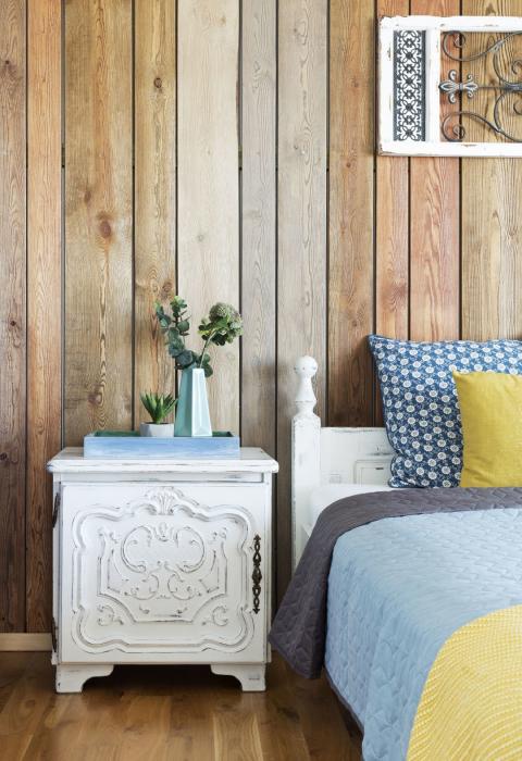 Aranżacja sypialni,Kolorowe mieszkanie,mieszkanie boho,dekoracja nad łóżkiem panel drewniany,ściana obita drewnianymi dechami w kolorze drewna, niebieskie kinkiety vintage, rzeźbione fronty szafek nocnych w kolorze białym