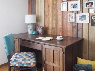 Kolorowe mieszkanie,mieszkanie boho,biurko drewniane, fotel niebieski kolorowe siedzisko, poduszki i koc w koszy metalowym, sciana obita drewnianymi dechami