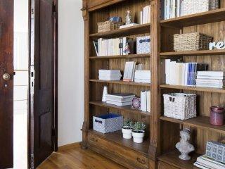 Kolorowe mieszkanie,mieszkanie boho,regał drewniany,książki, kolorowa indyjska pufa