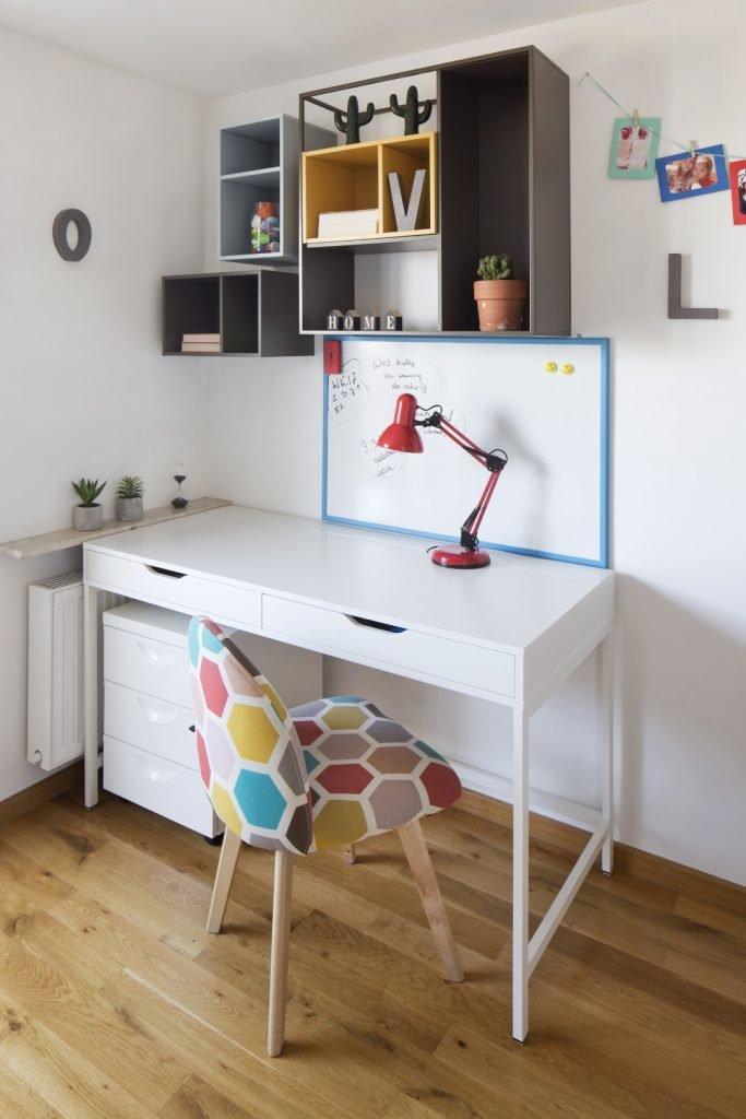 pokój dziecka,biurko białe, biała szafka pod biurkiem,kolorowy fotel, czerwona lampka biurkowa, pókli szare i niebieskie vox muto