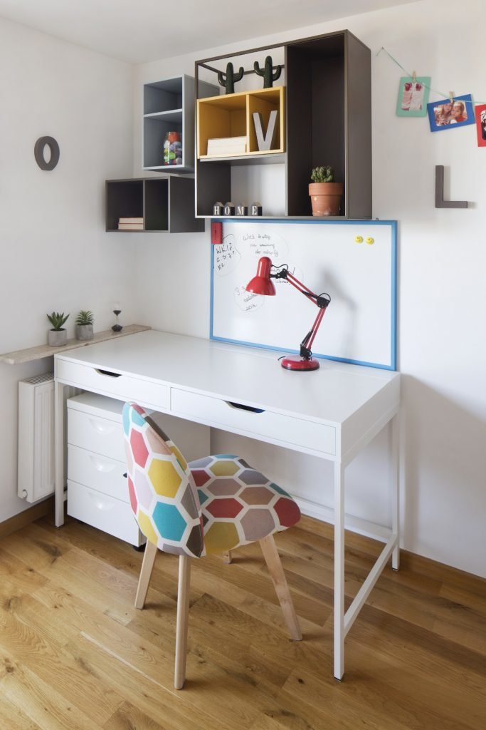 Kolorowe mieszkanie,pokój dziecka,biurko białe, biała szafka pod biurkiem,kolorowy fotel, czerwona lampka biurkowa, pókli szare i niebieskie vox muto