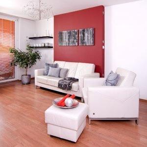 Realizacje projektów,małe mieszkanie,minimalizm, nowoczesne, biała kanapa i fotel skórzany na tle czerwonej ściany,Małe mieszkanie dla rodziny