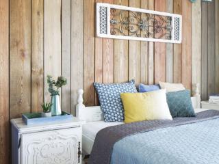 mieszkanie boho,dekoracja nad łóżkiem panel drewniany,ściana obita drewnianymi dechami w kolorze drewna, niebieskie kinkiety vintage, rzeźbione fronty szafek nocnych w kolorze białym