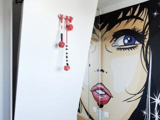 mieszkanie boho,pokój dziecka, białe łóżko chowane w szafie, uchwyty z czerwonych pomponów, szafa z lutrami,tapeta grafika z twarzą kobiety