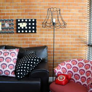 Kolor w salonie_styl loftowy_ kolorowy fotel_deseń_czerwony telefon