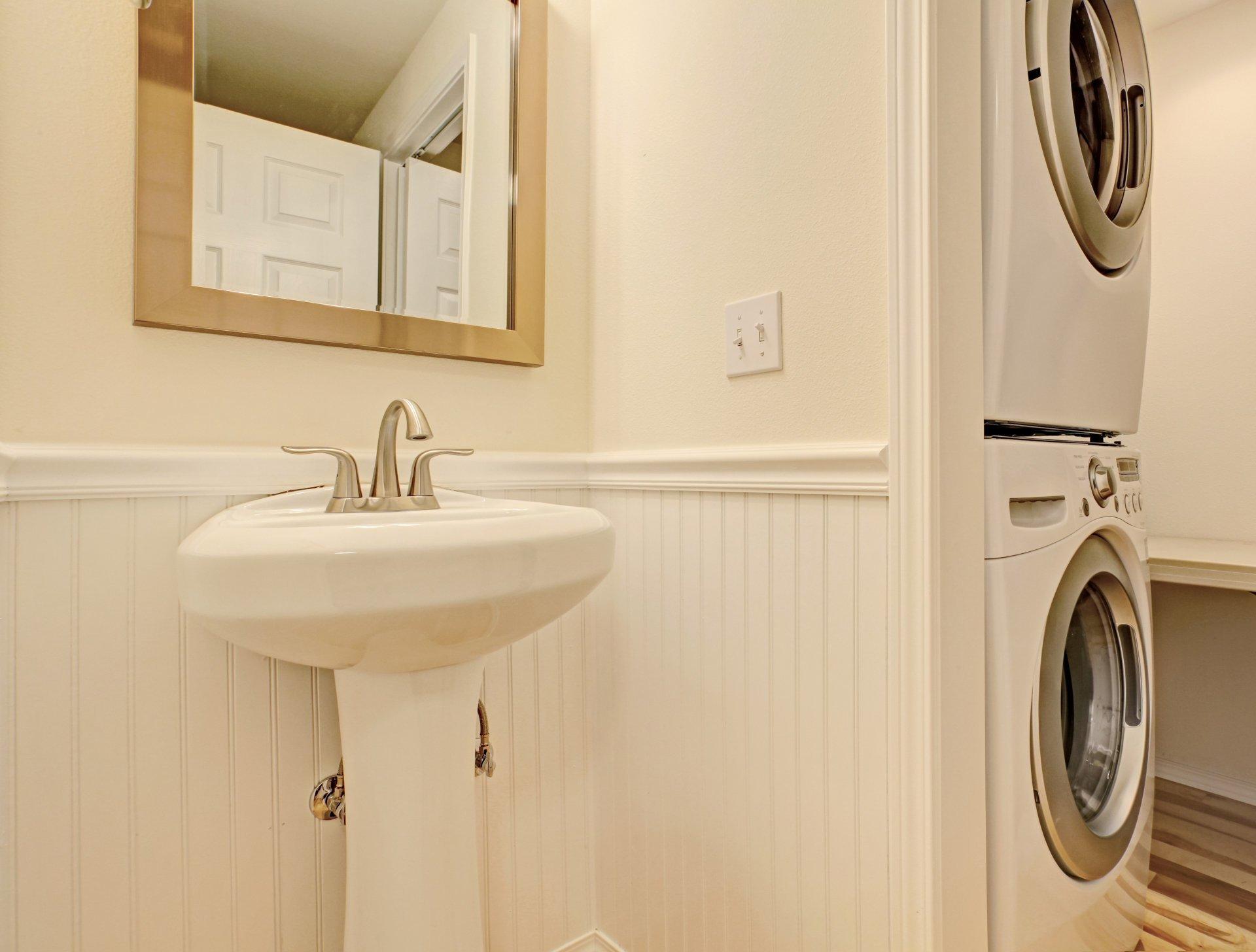 Miejsce dla pralki_Aranżacja małej pralni w łazience, biała umywalka, lustro w złotej ramie, pralka i suszarka za małą ścianką