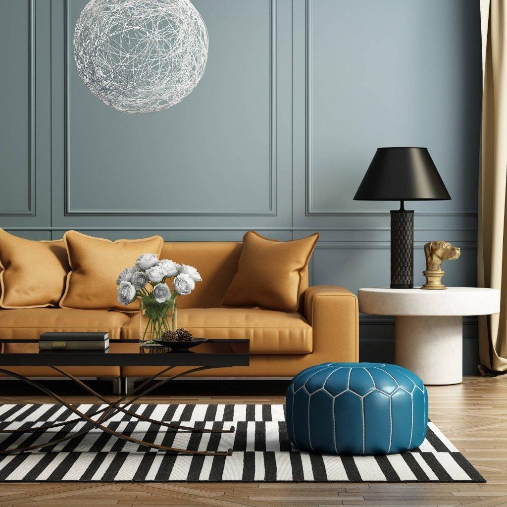 kolor w salonie,niebieska ściana, sztukateria na ścianie,salon skórzana beżową kanapą, dywan w czarno-białe pasy, niebieska pufa, w tle niebieska ściana, kolory do salonu, kolor do salonu, salon kolory, salon w beżach i szarościach