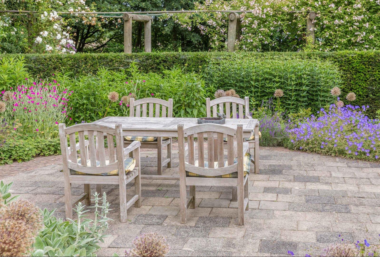 Ogród na wiosnę,Meble ogrodowe szare,Drewniany komplet ogrodowy szary,kamienna posadzka, w tle ogród liczne kolorowe kwiaty zielony żywopłot