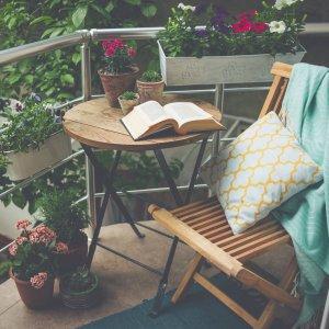 Piękny taras lub balkon z małym stołem, krzesłem i kwiatami_Ogród na wiosnę