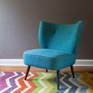 Kolor w salonie,Turkusowy fotel Chevron,kolorowy dywan, w tle ciemna ściana