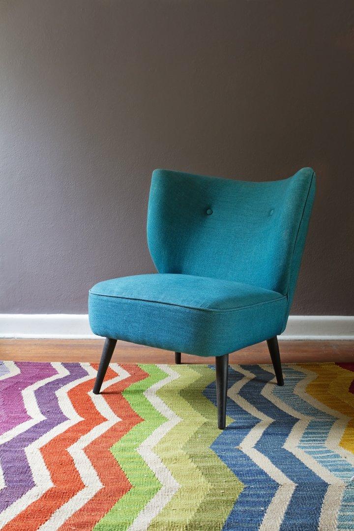Kolory Do Salonu, ,Turkusowy fotel Chevron,kolorowy dywan, w tle ciemna ściana