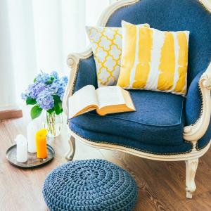 kolor w salonie,Kolorowe obicie klasycznego fotela, przytulny fotel z otwartą książką i dekoracyjnymi poduszkami,koncepcja wystroju wnętrza i domu