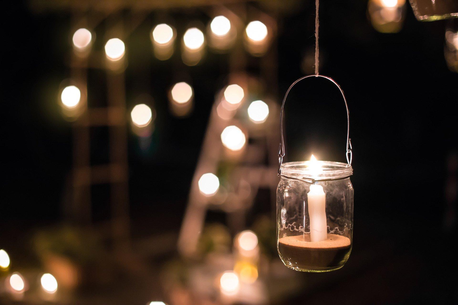 Ogród na wiosnę_oświetlenie ogrodu bez prądu_Światło świec_lampion ze słoika, w tle zamazany ogród
