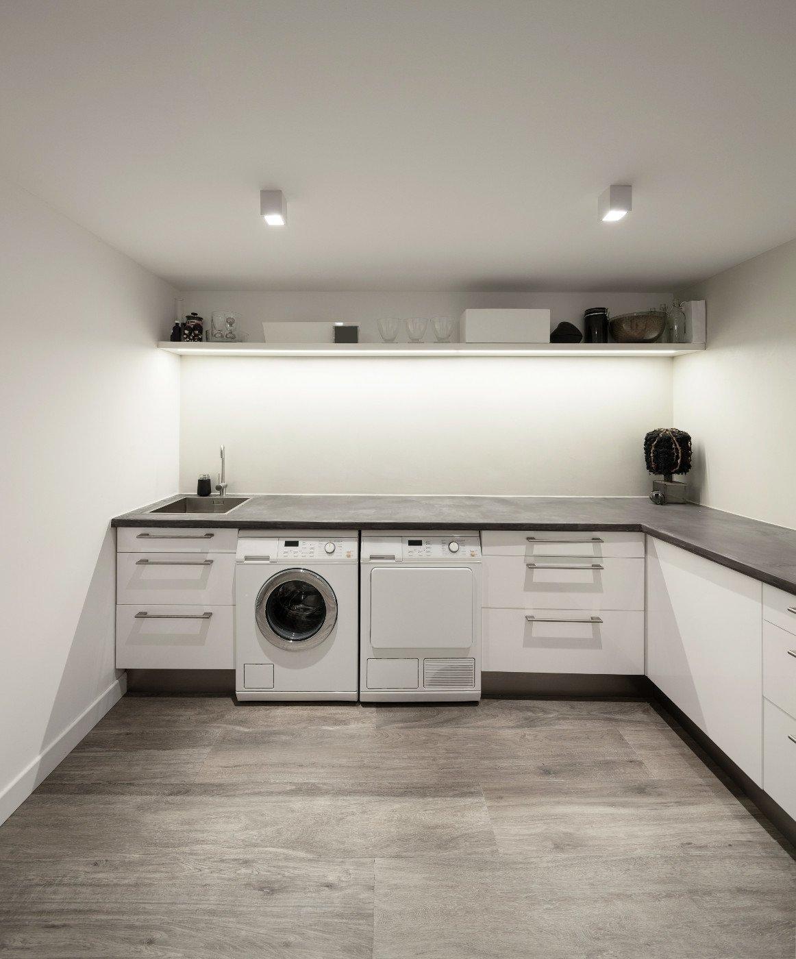 Miejsce dla pralki_Osobna pralnia_pomieszczenie z białymi szafkami pralka suszarka, podłoga drewniana