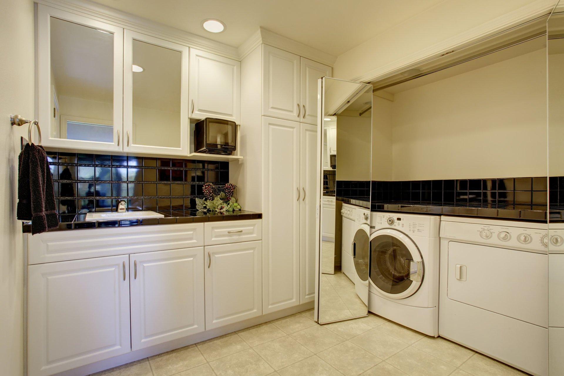 Miejsce dla pralki,pralka za drzwiami przesuwnymi, biała łazienka, przesuwane drzwi z lustra, schowana pralka i suszarka