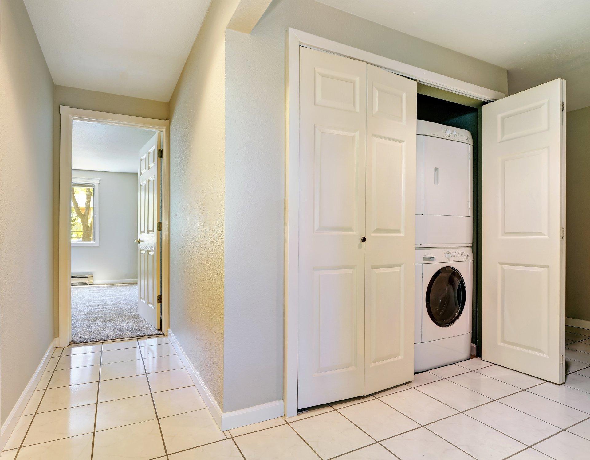 Miejsce dla pralki,Pralka w szafie gospodarczej,pralka w przedpokoju, pralka i suszarka schowana za białymi drzwiami w korytarzu