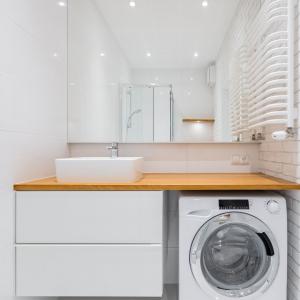 Miejsce dla pralki,Pralka pod blatem, mała biała łazienka,drewniany blat, duże lustro na całą ścianę,