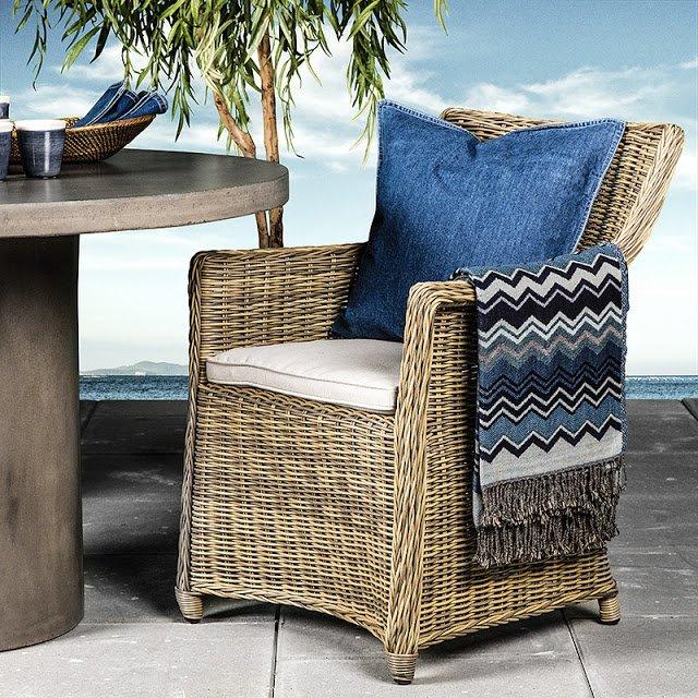 Ogród na wiosnę_meble ogrodowe rattanowe_Wiklinowy fotel ogrodowy_niebieska poduszka, koc w niebieskie wzory, kamienna podłoga,w tle morze niebieska woda, plama