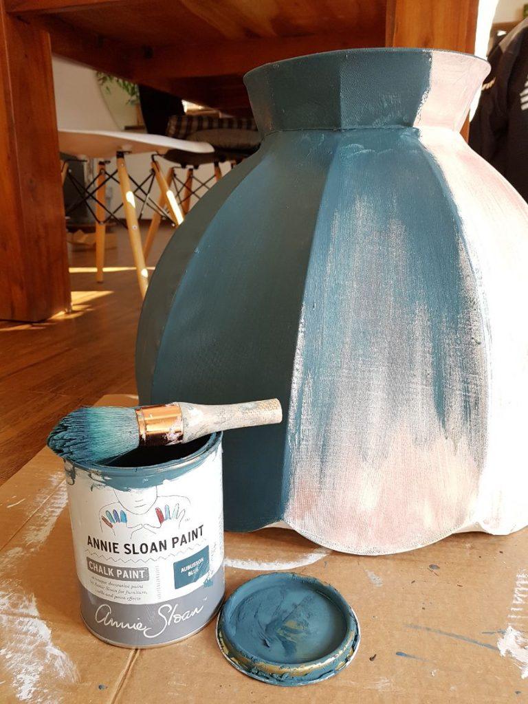 Jak odnowić lampę, malowanie abażuru, farby kredowe Annie Sloan, Aubusson Blue, abażur leży na podłodze w trakcie jego malowania, obok leży puszka z farbą i pędzel, w tle drewniany stół, Renowacja mebli, metamorfoza starych mebli, renowacja mebli warszawa, stare meble w stylu boho, metamorfoza mebli vintage, stare meble vintage po renowacji, renowacja ram i mebli warszawa, przerabianie mebli vintage, renowacja mebli vintage, jak odnowić stary abażur, jak odnowić abażur, jak odnowić lampę stojącą, jak pomalować abażur, jak odnowić starą lampę, czy można pomalować abażur,