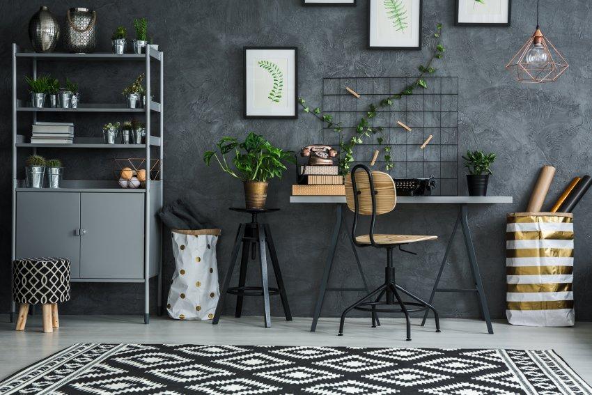 pokój młodzieżowy, szare biurko, metalowy szary regał, dywan z czerwo białe wzory, ciemna szara ściana