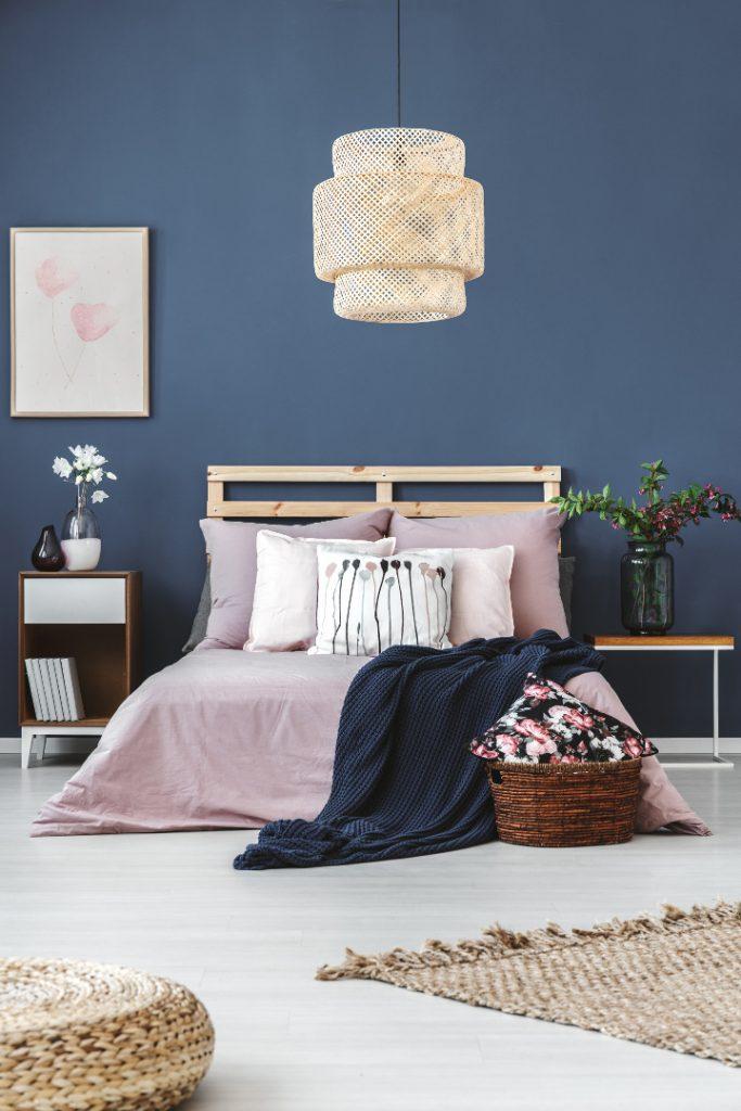 Niebieski w mieszkaniu, sypialnia, łóżko z różówą pościelą, rzucony granatowy pled, w tle ciemno niebieska ściana