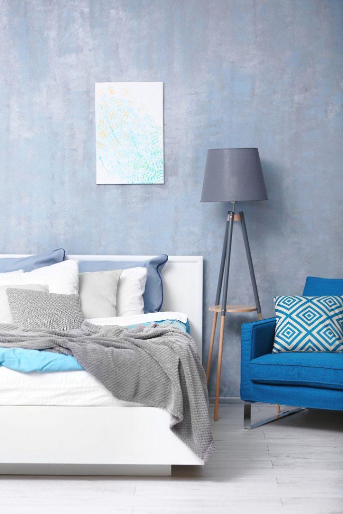 Niebieski w mieszkaniu, sypialnia, łóżko w nieładzie, rzucona szary pled,niebieski fotel, w tle niebieska zniszczona ściana