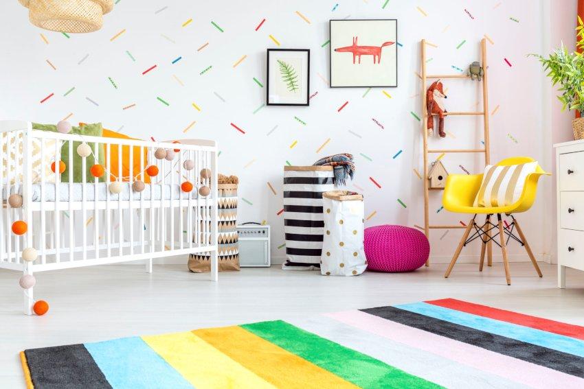pokój dziecka- dekoracje, kolorowa tapeta wzór konfetti, żółty fotel, białe łóżeczko,różowa pufa