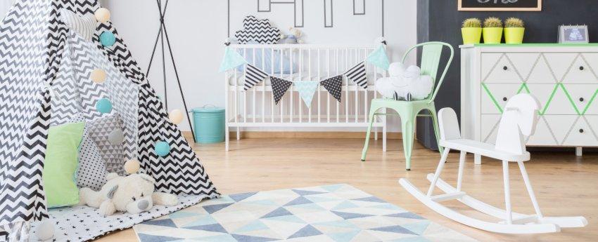 pokój dziecka- dekoracje, biała koloda w geometryczne wzory, łóżeczko dziecięce białe, namiot typu tipi, konik na biegunach biały