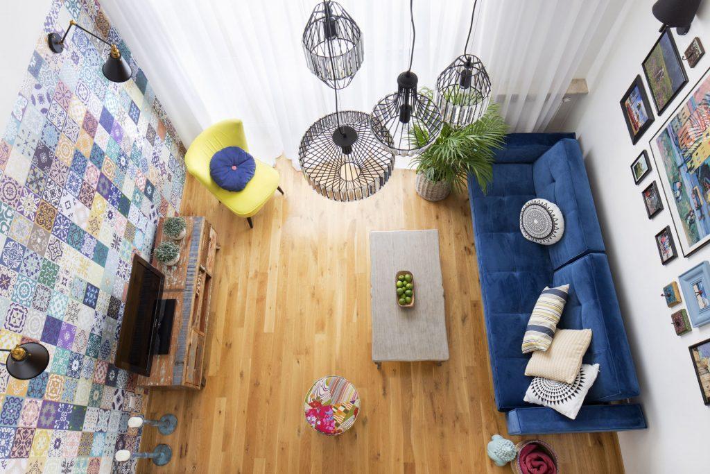 Kolorowe mieszkanie,mieszkanie, boho, mojerealizacje,kolor w salonie,wydok z góry, salon kanapa niebieska szafka rtv, żółty fotel, szry stolik, metalowe żyrandole
