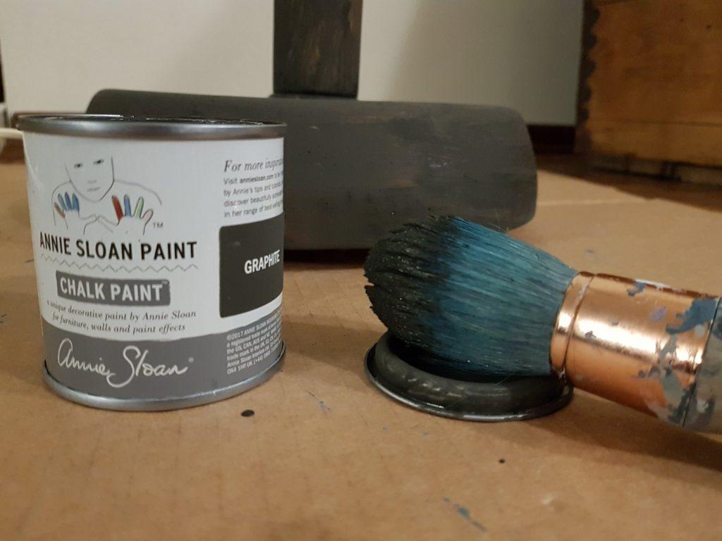 jak odnowić lampę, pędzel ubrudzony szarą farbą, puszka farby kredowej Annie Sloan kolor Graphite, w tle pomalowana na szaro podstawa lampy podłogowej