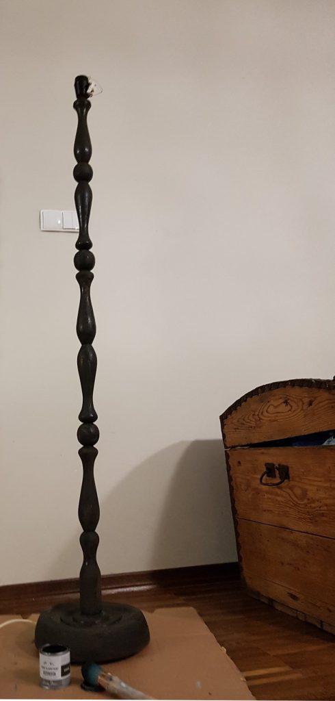 Jak odnowić lampę, podstawa lampy podłogowej pomalowana na czarno, na podłodze leży puszka z farbą i pędzel, w tle stary drewniany kufer, Renowacja mebli, metamorfoza starych mebli, renowacja mebli warszawa, stare meble w stylu boho, metamorfoza mebli vintage, stare meble vintage po renowacji, renowacja ram i mebli warszawa, przerabianie mebli vintage, renowacja mebli vintage, jak odnowić stary abażur, jak odnowić abażur, jak odnowić lampę stojącą, jak pomalować abażur, jak odnowić starą lampę, czy można pomalować abażur,