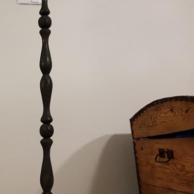 jak odnowić lampę, podstawa lampy podłogowej pomalowana na czarno, na podłodze leży puszka z farbą i pędzel, w tle stary drewniany kufer