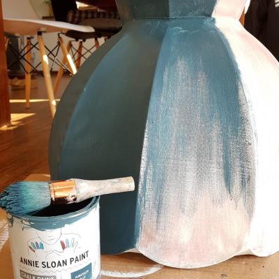 jak odnowić lampę, malowanie abażuru, farby kredowe Annie Sloan, Aubusson Blue, abażur leży na podłodze w trakcie jego malowania, obok leży puszka z farbą i pędzel, w tle drewniany stół