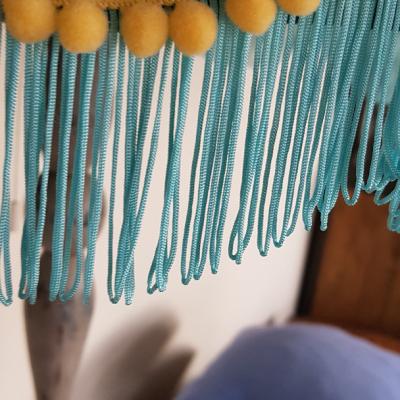 jak odnowić lampę, widoczny kawałek abażuru z niebieskimi frędzlami i żółtą taśmą pasmanteryjną, w tle niebieskie poduszki