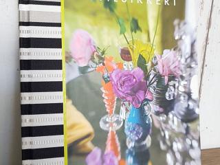 Tkaniny we wnętrzu,Album z fotografiami Tricia Guild oparty o ścianę z białych desek