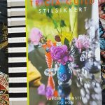 Tkaniny we wnętrzu,Album z fotografiami Tricia Guild leży na stole, w tle kolorowe tkaniny