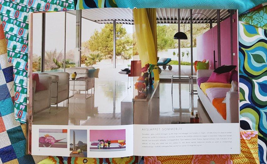 Tkaniny we wnętrzu,Album z fotografiami Tricia Guild leży na stole, widoczna fotografia nowoczesnego salonu, w tle kolorowe tkaniny