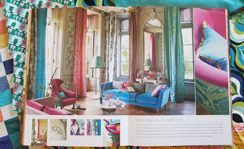 Tkaniny we wnętrzu,Album z fotografiami Tricia Guild leży na stole, widoczna fotografia salonu w stylu glamour, w tle kolorowe tkaniny