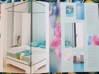 Tkaniny we wnętrzu,Album z fotografiami Tricia Guild leży na stole, widoczna fotografia nowoczesna sypialnia, w tle kolorowe tkaniny