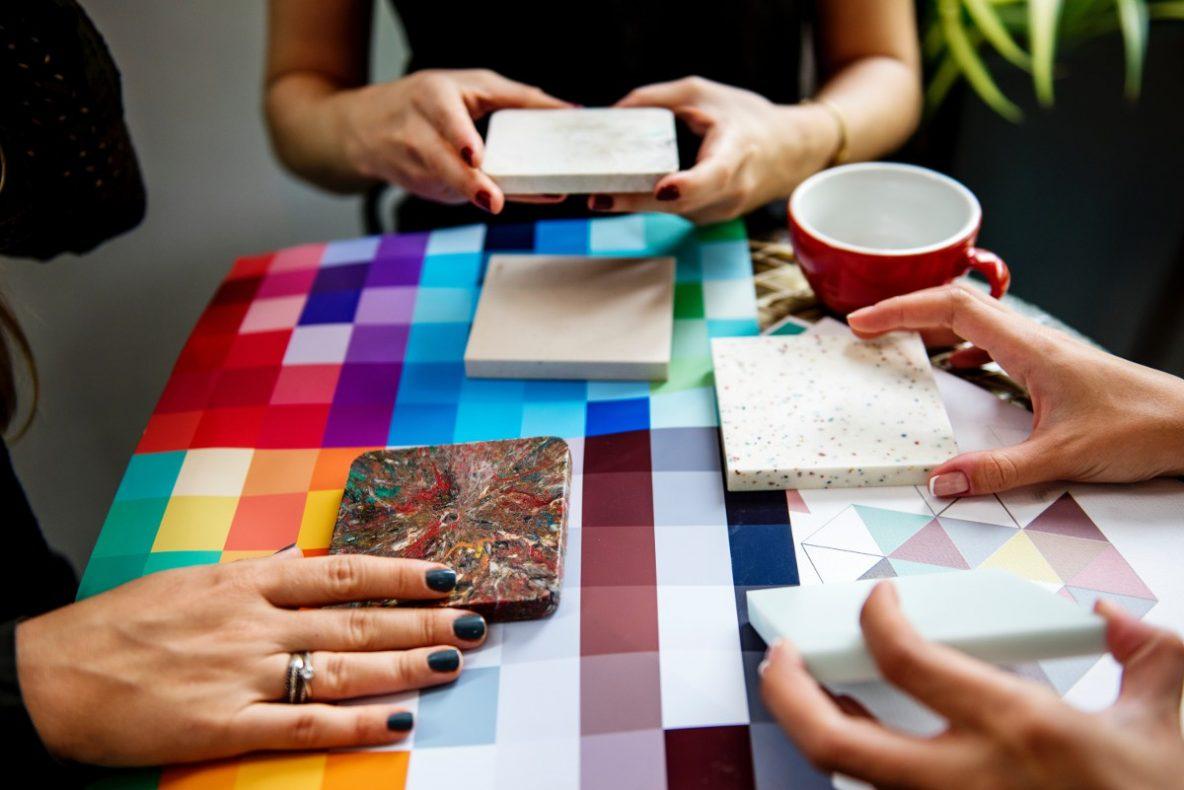 Jak znaleźć projektanta, ile kosztuje projektant wnętrz, ile kosztuje projekt wnętrz, projekt mieszkania, projekt pokoju, projekt łazienki, projekt kuchni, na zdjęciu trzy pary damskich dłoni trzymaja próbki kamiennych elementów dekoracji wnętrz, projektantki wybierają materiały do wykończenia mieszkania, na stole kolorowy wzornik kolorów, kolorowe kwadraty z kolorem farb