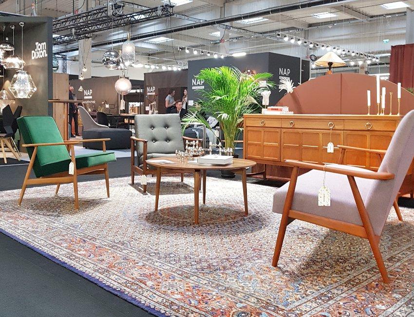 Targi wnętrzarskie, fotele z lat 50, zielony fotel, kolorowy dywan, drewniana komoda