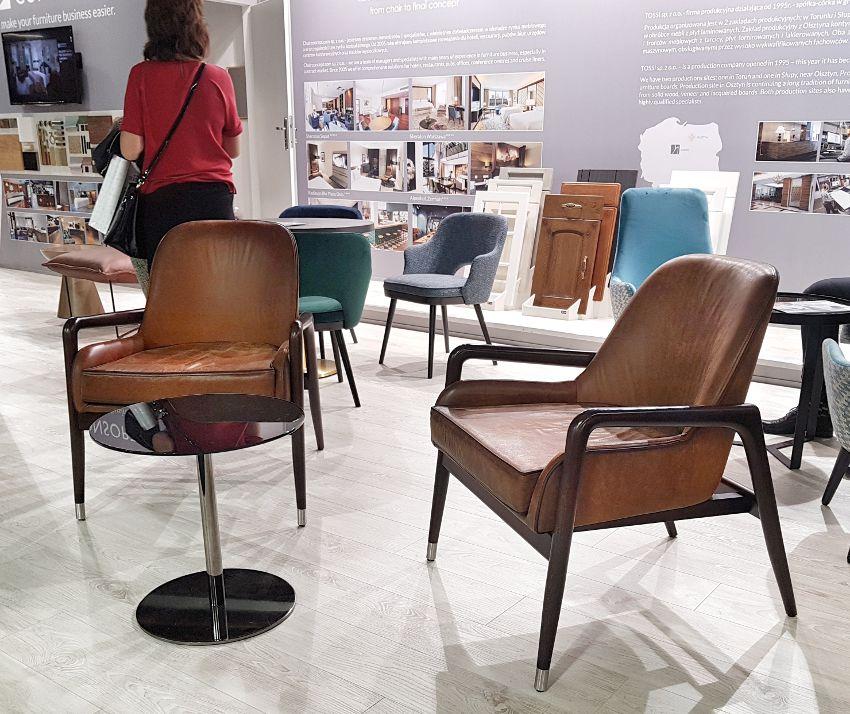 Targi wnętrzarskie, skórzane brązowe fotele z tal 60, okrągły stoli szklany,