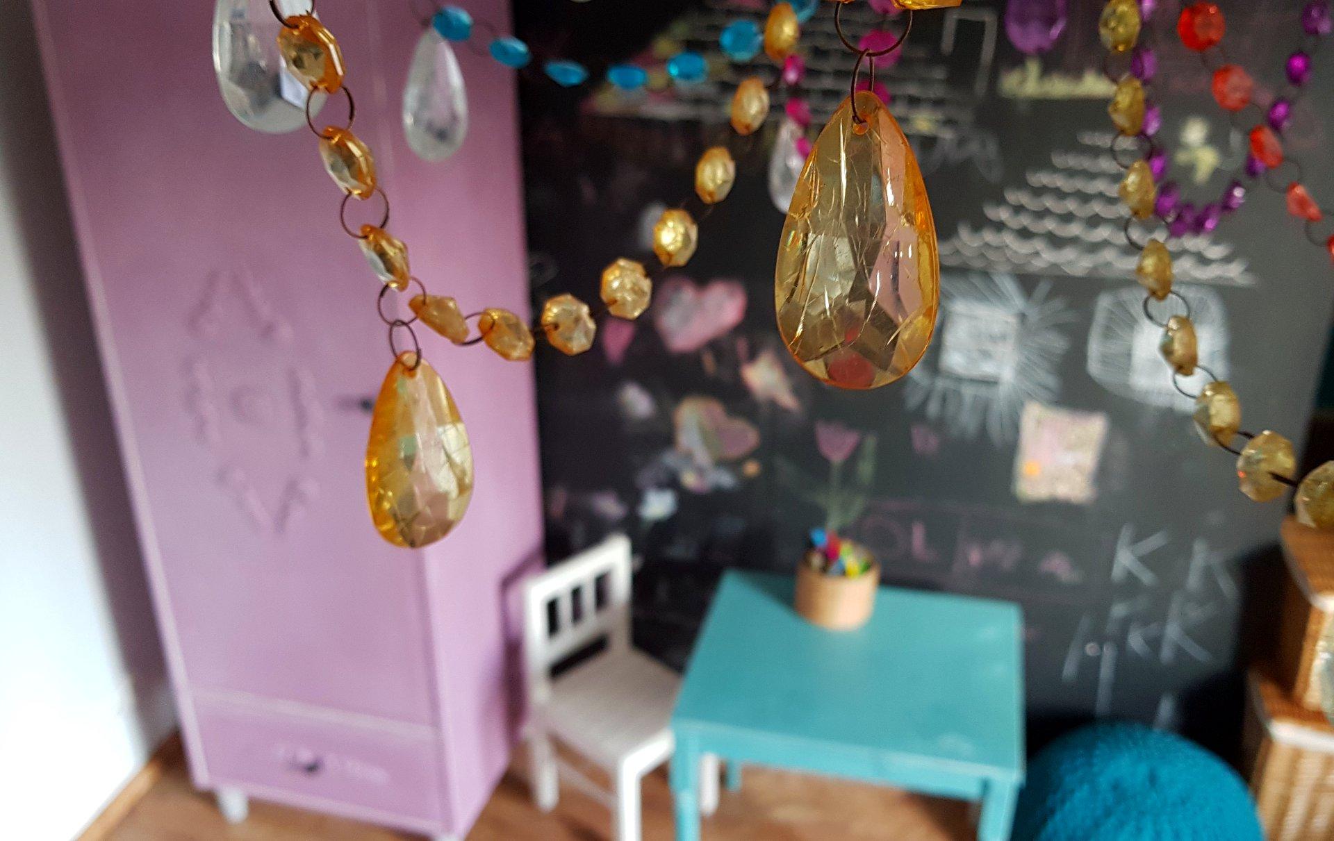 Jak pomalować meble- różowa szafa w pokoju dziewczynki, w tle czarna ściana tablicowa, kolorowy kryształowy żyrandol, pokój księżniczki,
