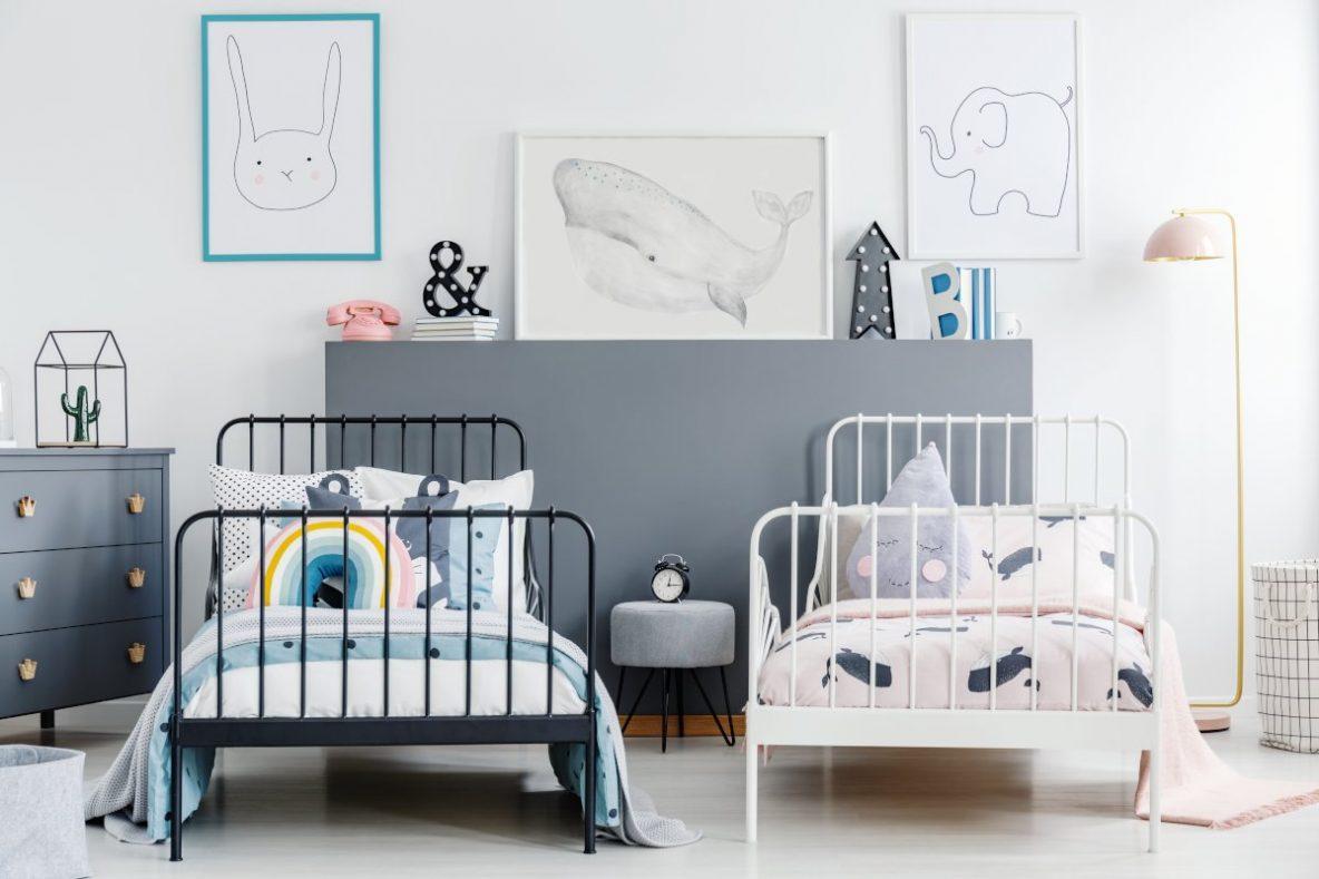 Jak urządzić pokoik dziecka, Sypialnie dekoracje, pokój dla rodzeństwa, pokój dla dziecka Ikea, jak zagospodarować dziecięcy pokój, jakie meble do pokoju dziecka, projekt pokoju dziecka, dekoracje do pokoju dziecka, dziecięcy pokój, na zdjęciu dwa łóżka metalowe dziecięce, jedno łóżeczko dla chłopca drugie dla dziewczynki, obok szara komoda z drewnianymi uchwytami, pomiędzy łóżeczkami taboret z szarą tapicerką i metalowymi nogami, po prawej stojąca wysoka biała lampa podłogowa, w tle szara ścianka i kilka obrazów, na ścianie pbrazek ze królikiem, wielorybem i słoniem, poduszki dekoracyjne w kształcie tęczy i łezki, kolory ścian w pokoju młodzieżowym, pokój dla dziewczynki kolory ścian, pokój dziecięcy kolory ścian, szare ściany w pokoju młodzieżowym, kolory ścian w dziecięcym pokoju, kolory pokoi
