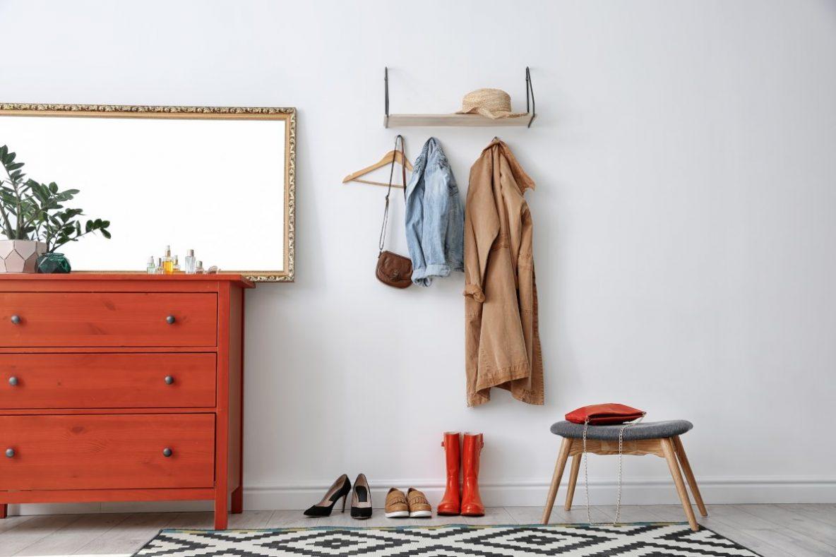 Jak urządzić przedpokoju, mały przedpokój, jakie meble do przedpokoju, funkcjonalny przedpokój, jak zaprojektować przedpokój, dekoracje co przedpokoju, czerwona komoda, na ścianie lustro w złotej ramie, obok na ścianie wisi drewniana półka i haczyki na kurtki, na podłodze poustawiany buty i czerwone kalosze, pod ścianą krzesełko z materiałowym szarym siedziskiem, szara tapicerka, na podłodze dywan czarno biały w graficzne wzory