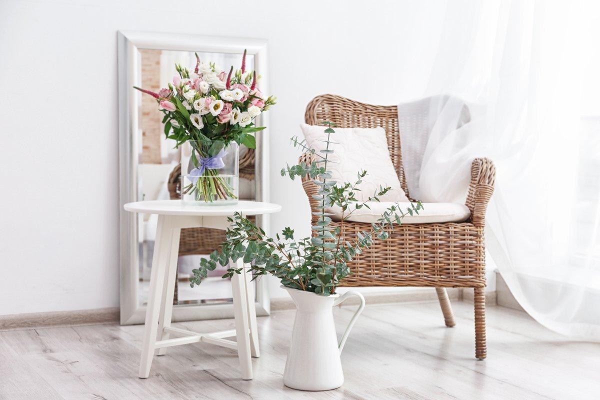 Dekoracje do salonu, zwiewna delikatka firanka, firanka przepuszczająca światło, fotel ratanowy z białą poduszką, biały stolik z wazonem i bukietem kwiatów, w tle stoi oparte o ścianę duże lustro w białej ramie