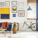 Wiosenna dekoracja, jak wprowadzić do domu wiosnę, dekoracje wiosenne, mieszkanie, niebieska kanapa, drewniany stolik, rower w mieszkaniu, niska szafka pod ścianą, na szafce liczne niebieskie wazony, na ścianie duża ilość obrazów i plakatów, kolorowe plakaty, w tle ściana z obrazami, domowa galeria,