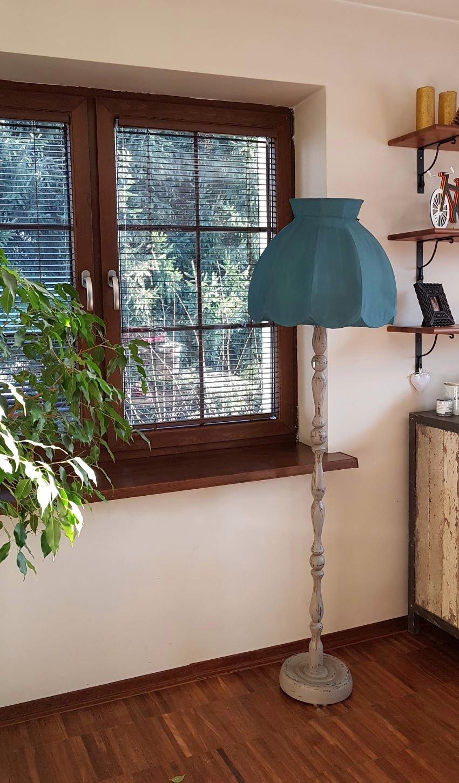 jak odnowić lampę, lampa w stylu vintage, szara z licznymi przetarciami, niebieski abażur, widoczny kawałek liściastej rośliny, w tle ładny widok przez okno
